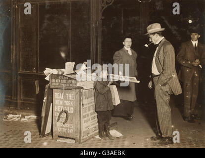 Jerald Schaitberger of 416 W. 57th St. NY who helps an older boy sell papers until 10 PM on Columbus Circle. 7 yrs. - Stock Photo