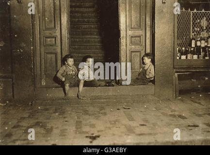 Late at night. Street boys. Jest hanging around.  Location: Boston, Massachusetts. Date 1909 October. Late at night. - Stock Photo