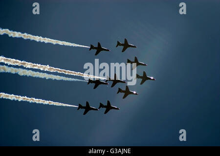 The Red Arrows aerobatic display team flying in formation against a dark blue sky - Stock Photo