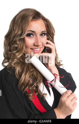 Young female graduate holding her diploma and talking on her smart phone; Edmonton, Alberta, Canada - Stock Photo