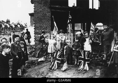 Standing amid the rubble of bombed homes, people celebrate with flags in Battersea, South London, to celebrate the - Stock Photo