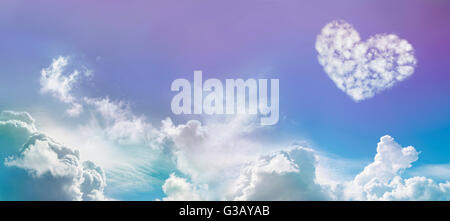 Wide blue sky background with fluffy clouds and a large heart-shaped cloud on right hand side with copy space on - Stock Photo
