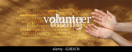 woman's hands in an open needy position with the word VOLUNTEER surrounded by a relevant word cloud on a soft golden - Stock Photo