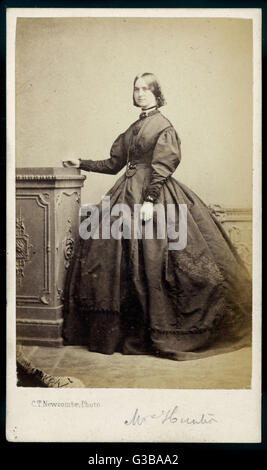Plain dress with bishop  sleeves & reversed cuffs  composed of folds. A string of  large beads falls between - Stock Photo