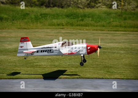 Single Prop gas engine radio controlled airplane landing in a grass field - Stock Photo