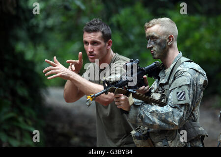A French soldier teaches a U.S. Army soldier squad movement drills at the Jungle Warfare School during exercise - Stock Photo