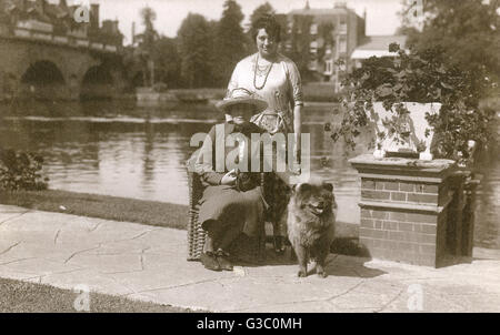 Two women and a dog at East Sheen, West London, with the River Thames behind them.      Date: circa 1930s - Stock Photo
