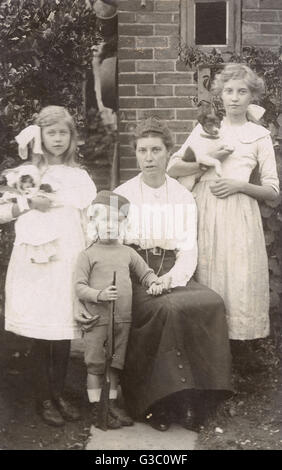 Family of four with a terrier dog and a doll in a garden. The little boy is holding a toy rifle.      Date: circa - Stock Photo