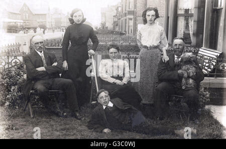 Family of six with a small, shaggy dog in a front garden.      Date: circa 1910s - Stock Photo