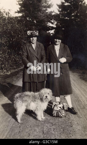 Two middle aged women with a dog and a basket on a country lane.     Date: circa 1920s - Stock Photo