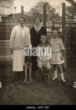 Four people (two women and two children) with a German Shepherd dog in a garden, Germany.      Date: circa 1930s - Stock Photo