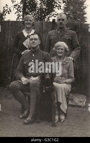 Family of four with a black labrador dog in a garden.  The two men are wearing uniform.      Date: circa 1930s - Stock Photo