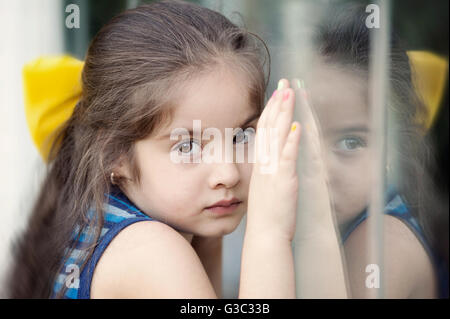Girl standing against window, hands pressed against glass - Stock Photo