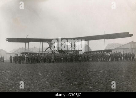 Handley Page biplane, O/400 bomber, with a large group of men standing in front of it on an airfield.      Date: - Stock Photo