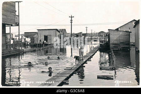 Flooding in Tampico, Tamaulipas, Mexico, June 1925, with boys having fun swimming in the water.      Date: 1925 - Stock Photo