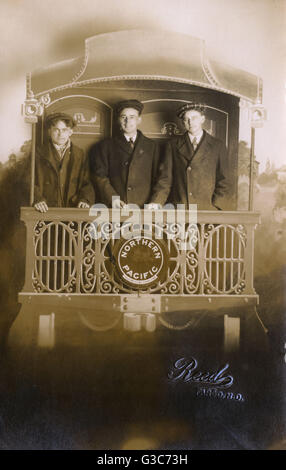 Studio photo, three young men on a mockup of a Northern Pacific train, Yellowstone Park Line, with a painted backdrop. - Stock Photo