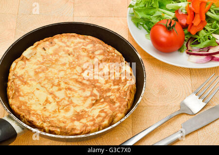 A Spanish omelette or tortilla served with a tomato and green salad - Stock Photo