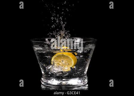 Lemon splashing in water on a black background - Stock Photo