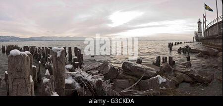 Wooden poles covered with ice, island Lindau in Lake Constance, Swedish flag, lighthouse, Lindau, Bavaria, Germany - Stock Photo