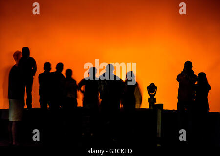 Ghostly time exposure of visitors in silhouette at dusk, lava glowing Kilaueea Caldera volcano, Hawai'i Volcanoes - Stock Photo