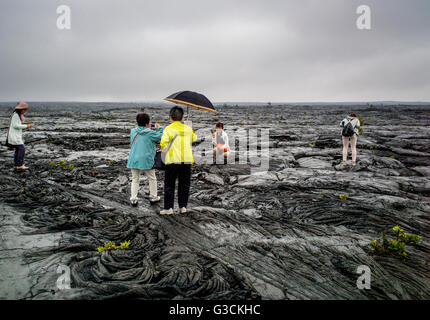 Japanese tourists visit a barren rainy landscape of lava rock fields, Hawai'i Volcanoes National Park, Big Island, - Stock Photo