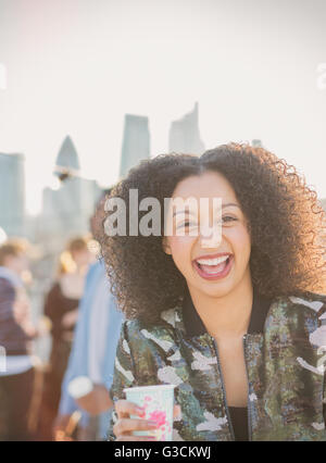 Portrait laughing young woman drinking at party - Stock Photo