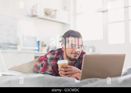 Young man drinking coffee at laptop on bed - Stock Photo