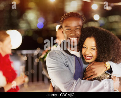 Portrait smiling young couple hugging at party - Stock Photo