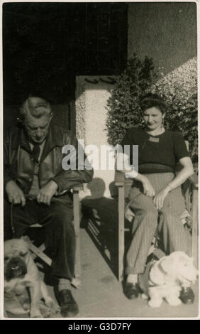 Couple in garden chairs with two dogs.      Date: circa 1930s - Stock Photo