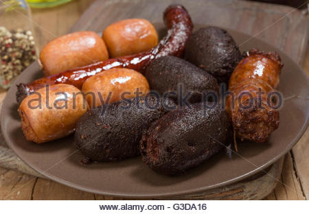 Lots of Spanish sausage roasted in an earthenware dish - Stock Photo