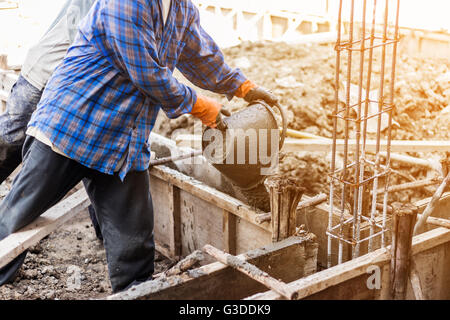 worker mixing cement mortar plaster for construction with vintage tone. - Stock Photo