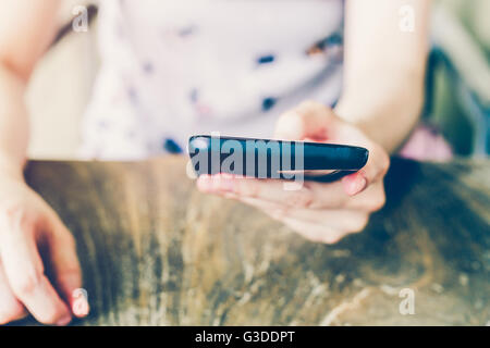 Hand woman using phone in coffee shop with depth of field. - Stock Photo