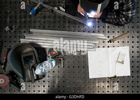A metal worker welding different metal parts on a table according instructions. - Stock Photo