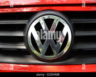 VW Logo on a red Volkswagen car - Stock Photo