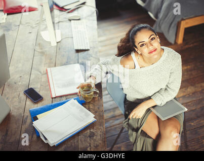 Portrait confident college student studying with tea and digital tablet