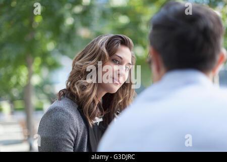 Businesswoman listening to businessman in park - Stock Photo