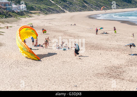KNYSNA, SOUTH AFRICA - MARCH 3, 2016: A paraglider trying to get airborne while unidentified beachgoers watch - Stock Photo