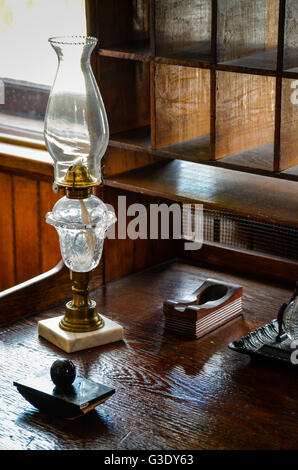 An old writing set including ink well and blotter along with kerosene lamp sit on old wooden desk with pigeon hole - Stock Photo