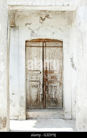 Old wooden door in weathered white house front on Pelion Peninsula, Greece - Stock Photo