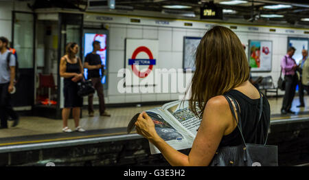Woamn reading a newspaper at Victoria Underground Station, whilst waiting for a train, London, UK - Stock Photo