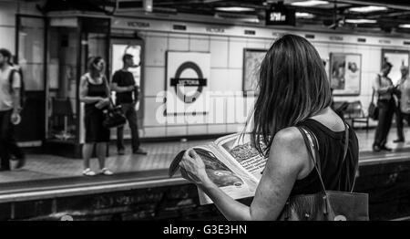 Black And White image of a woman reading a newspaper At Victoria Underground Station, whilst waiting for a train - Stock Photo