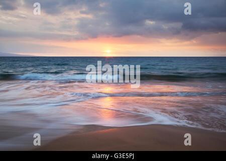 Soft ocean waves at sunset from Kamaole Beach; Maui, Hawaii, United States of Amerida - Stock Photo