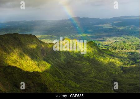 Rainbow over a ridge near the center of Kauai; Kauai, Hawaii, United States of America - Stock Photo