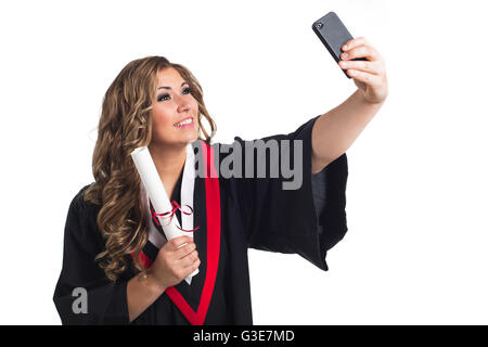 Young graduating woman taking a self-portrait with her smart phone and celebrating her graduation; Edmonton, Alberta, - Stock Photo