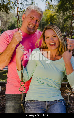mature man pushing his younger wife on a swing - Stock Photo