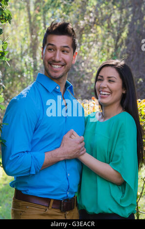 Young Hispanic couple holding hands laughing outside - Stock Photo