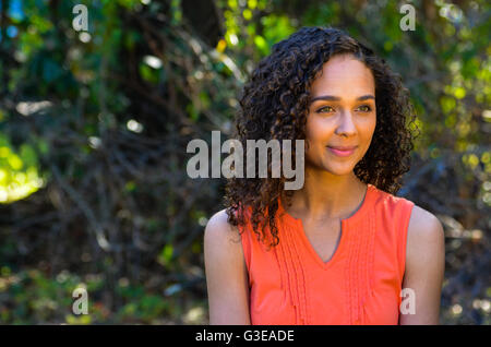 mixed race ethnic young girl sitting outside in a chair - Stock Photo