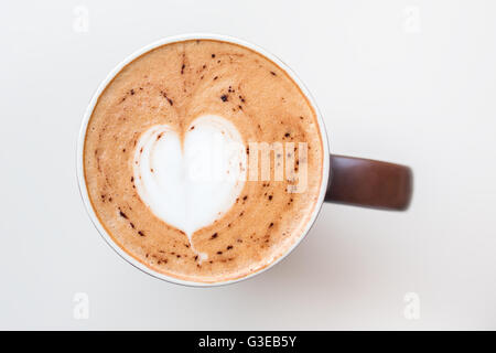 Cup of cappuccino coffee with the milky foam on top in a heart shape viewed from above in a brown cup on white table - Stock Photo
