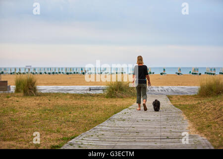 Woman walking to the beach with a black havanese dog on the lead - Stock Photo