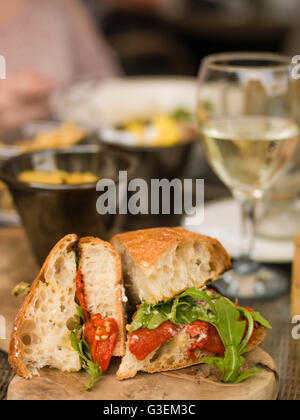 Creative Image of a Vegetarian Roast Red Pepper Ciabatta Sandwich or Bread Roll With A Glass of White Wine - Stock Photo
